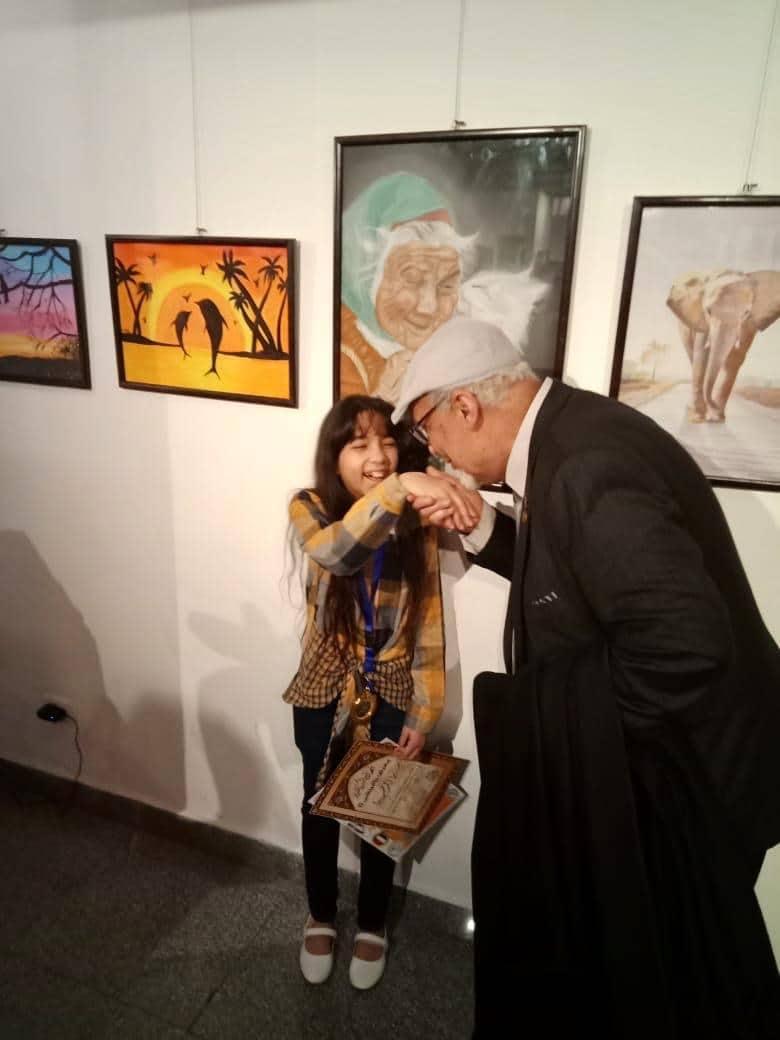 شيخ النقاد التشكيلين سيد جمعه يقبل يد الطفلة سادين احمد